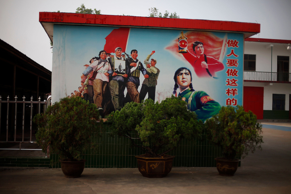 Images from revolutionary China adorn a wall in the model village of Nan Jie Cun, China, Wednesday, Aug. 26, 2009.  Nan Jie Cun village in central China's Henan province advertises itself as a commune which continues to adhere to the communist teachings of Mao Zedong, who founded the People's Republic 60 years ago. The village's industries are collectively owned. Workers receive bonds, instead of currency, and housing and healthcare are free. They sing revolutionary songs and march to work in lines. Despite being out of step with the rest of today's China, the village's industries are a success, and more than 7,000 migrants have requested to work at Nan Jie Cun.