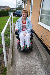 Older woman wheelchair user leaving her house and going down a ramp,