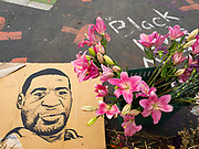 """12 JUNE 2020 - MINNEAPOLIS, MINNESOTA: A portrait of George Floyd and flowers at the impromptu memorial for George Floyd at the corner of 38th Street and Chicago Ave. in Minneapolis. The intersection is informally known as """"George Floyd Square"""" and is considered a """"police free zone."""" There are memorials to honor Black people killed by police and people providing free food at the intersection. Floyd, an unarmed Black man, was killed by Minneapolis police on May 25 when an officer kneeled on his neck for 8 minutes and 46 seconds. Floyd's death sparked weeks of ongoing protests and uprisings against police violence around the world.          PHOTO BY JACK KURTZ"""