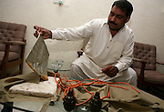 """Mazhar Iqbal Mashwani, senior superintendent police/counter-terrorism, displays hand grenades and a """"suicide jacket"""" recovered from a suspect at the CID office in Karachi, Pakistan."""