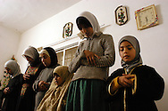 Women from the Toumeh family of the village of Qaffin, in the northern West Bank, pray in a family member's living room after breaking fast on November 23, 2003 during the holy month of Ramadan...Photo by Erin Lubin