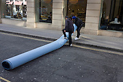 A team of Asian men are about to carry a roll of industrial carpet in a side street and destined for a nearby shop in London's New Bond Street.