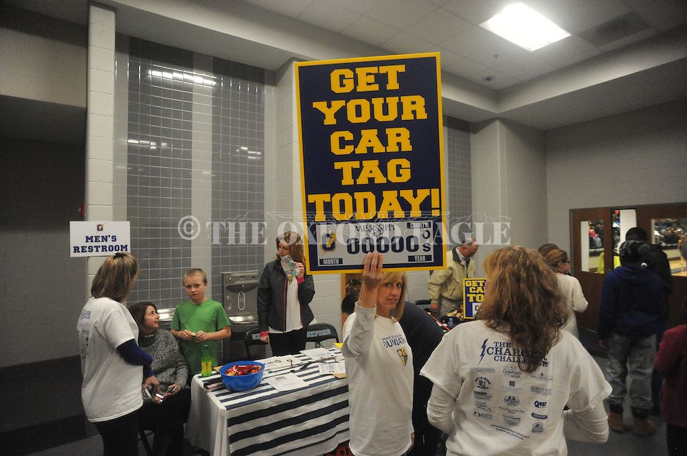 School board member Whitney Byars holds up a sign to sell Oxford High School license plates, at Oxford High School in Oxford, Miss. on Friday, February 6, 2015.