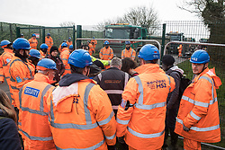 Harefield, UK. 8 February, 2020. HS2 engineers form a ring around environmental activists crawling through a ditch under a road closure implemented by HS2 engineers on Harvil Road in the Colne Valley to facilitate tree felling works for the high-speed rail project. Environmental activists based at a series of wildlife protection camps in the area prevented the tree felling works for the duration of the weekend for which they were scheduled.