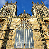 West Façade of York Minster in York, England<br /> The Great West Window is also called the Heart of Yorkshire. The stunning, heart-shaped tracery contains 129 pieces.  The lacey masonry was crafted by Ivo de Raghton in 1338.  It was painstaking reproduced during the 1980s. Flanking the front entrance are twin towers. Graceful pinnacles crown their 196 foot height. Inside of their two belfries are 35 bells