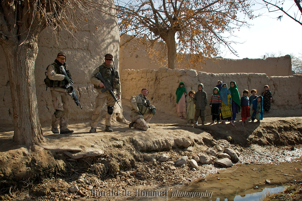 "Deh Rawod, Afghanistan, 13-01-07, .Dutch soldiers posing with Afghan children. The Dutch are on a Foot Patrol in the village of Towr Nasr, a small settlement on the Helmand river near Deh Rawod..The Dutch army has been in the southern Afghan province Uruzgan since mid 2006. The initial idea was to focus on reconstruction of the province, and win the ""hearts and minds"" of the Afghan people. The province turned out to be a hotbed for Taliban support so the mission that started so peacefully, turned into a fighting mission. Political tension on how to continue this mission has been rising in the Netherlands since the first bodybags started coming home.."