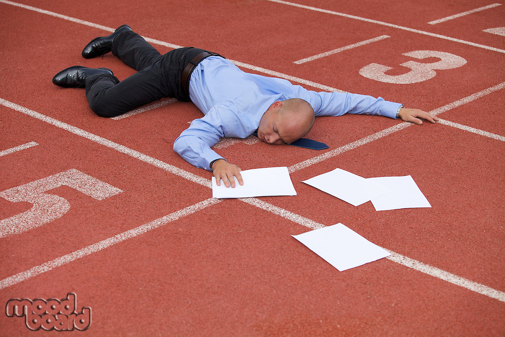 View of a businessman lying on a race track