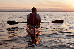 United States, Washington, Seattle.  A man paddles a sea kayak in Elliott Bay at sunset, looking west to the Olympic Mountains.