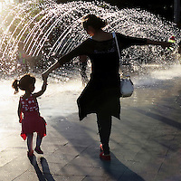 Mother and daughter holding hands and dancing by fountain, Georgetown, Washington DC, USA.
