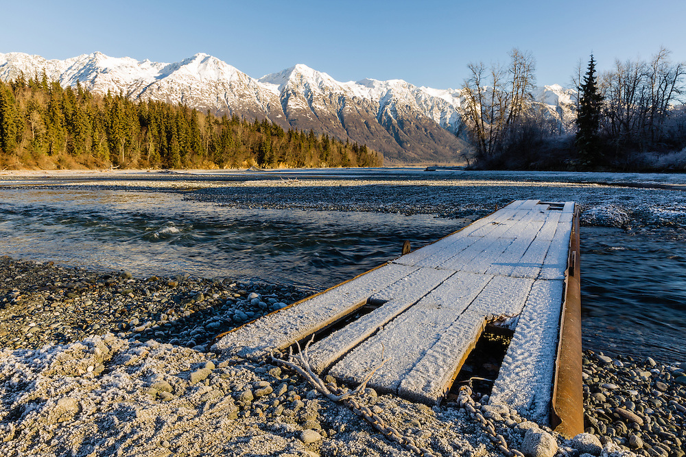 Afternoon sun illuminates the Takshanuk Mountains and a foot bridge leading over one channel of the Chilkat River in the Chilkat Bald Eagle Preserve near Haines in Southeast Alaska. Winter. Afternoon.