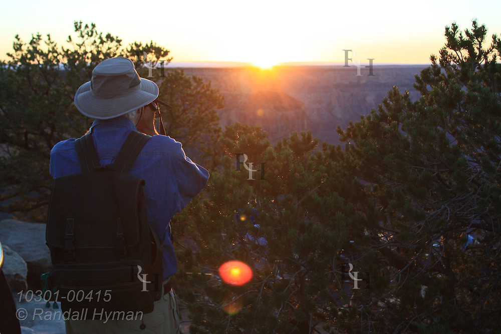 Man photographs late September sunset at Mohave Point overlook on South Rim of Grand Canyon National Park, Arizona.