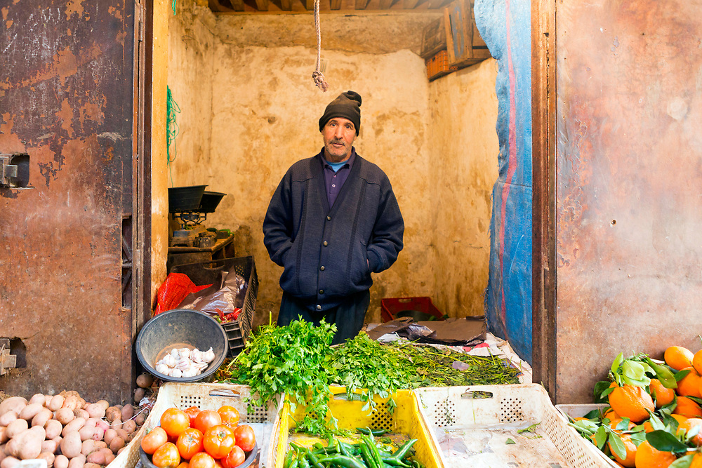 FEZ, MOROCCO - 05th MARCH 2016 - Portrait of a market trader selling fresh fruit and vegetables at a market stall in the old Fez Medina, Middle Atlas Mountains, Morocco.