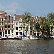 Amsterdam Amstel met touristische rondvaartboten, woonboten en stadsgezicht.