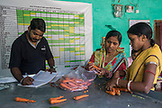 Technoserve Market Linkage Manager Rajiv Shinde (in dark blue t-shirt) keeps a record of orders from buyers as collection centre workers go about their daily work in the collection centre in Machahi village, Muzaffarpur, Bihar, India on October 27th, 2016. Non-profit organisation Technoserve works with women vegetable farmers in Muzaffarpur, providing technical support in forward linkage, streamlining their business models and linking them directly to an international market through Electronic Trading Platforms. Photograph by Suzanne Lee for Technoserve