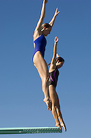 Two women jumping on diving boards