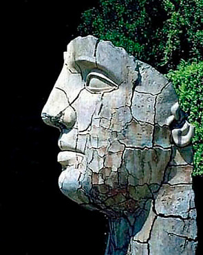 A cracked stone face sculpture in the Boboli Gardens of the Pitti Palace in Firenze (Florence), Italy
