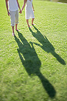 Couple holding hands walking on grass low section