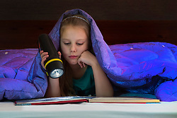 Girl reading book in bed under blanket. Dark room, kid holding flashlight.