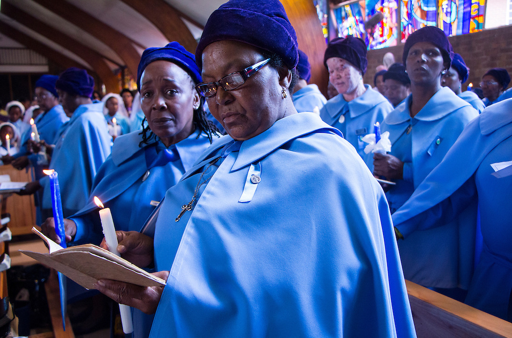Members of Regina Mundi's choir hold a candle during a service for former South African President Nelson Mandela, at the Regina Mundi Church in Soweto, on Sunday Dec. 8, 2013.