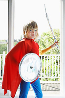 Portrait of young boy (7-9) in superhero costume holding toy shield and sword smiling
