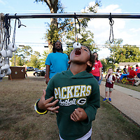 """Thomas Wells   Buy at PHOTOS.DJOURNAL.COM<br /> Shinji Spragin, 7,  tries to eat a powdered donut off a string at this year's Joyner Fall Festival friday evening. This year's theme was called the """"Joyner Town Fair""""."""