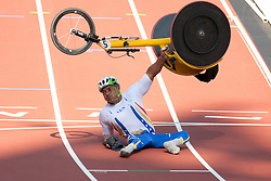 © London News Pictures. 04/09/2012. Venezualan paralympian - J Aguilar lifts his wheelchair over his head acknowledging the support of the crowd in the Olympic Stadium. He was competing in the 2nd heat of the Men's T53 800m race when he crashed into the finish line. Photo credit should read Manu Palomeque/LNP