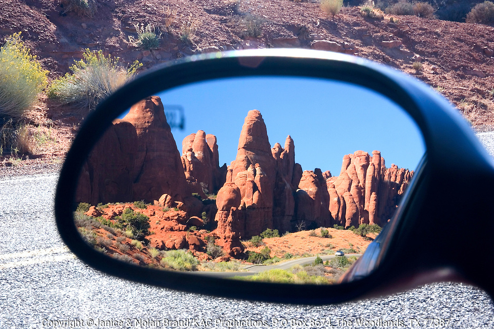 Car Mirror Image reflecting early morning light on arches in Devil's Garden area of Arches National Park in Utah.