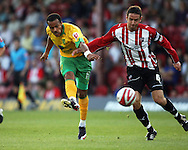 London - Tuesday, August 18th, 2009: Alan Bennett of Brentford and Simon Whaley of Norwich City gets a shot in during the Coca Cola League One match at Griffin Park, London. (Pic by Chris Ratcliffe/Focus Images)