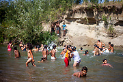 Children swimming in a small river close to the Roma settlement in Ostrovany during tropical summer weather.