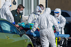 © Licensed to London News Pictures. 04/04/2020. Watford, UK. Paramedic's wearing personal protective equipment (PPE) outside an address in Watford carry a patient to an ambulance. Paramedics responded to a medical incident in Watford, an ambulance an two incident response units attended   Photo credit: Peter Manning/LNP