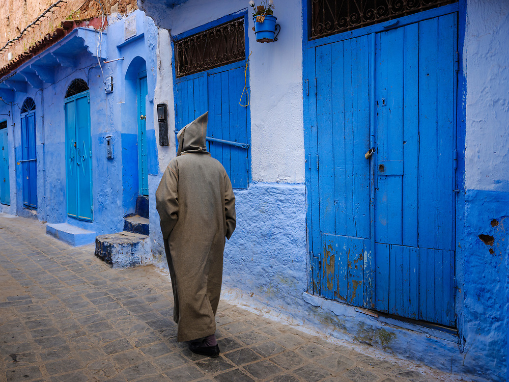 CHEFCHAOUEN, MOROCCO - CIRCA APRIL 2017: Moroccan man walking in the streets of Chefchaouen wearing a traditional djellaba