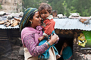 A mother and son are part of migrant community resurfacing a road in the Himalayas, India.  The migrant community is given education and information support by the Pragya organization who have a project helping in high altitude areas across the Himalayas.