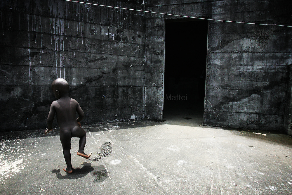 "A child plays 19 September 2005 on the rooftop of the former uncompleted Ministry of National Defense building in Congo Town on the outskirts of Monrovia. The ""Pentagon"", named this way by its occupants, shelters 394 families totalling approximately 3,000 people who were booted out in May 2005 of the Barclay Training Center, which had been their home for the last two decades. Former soldiers, who fought for former Liberian presidents Samuel Doe and Charles Taylor, live in this building with no water or electricity, overcoming past differences. The construction of the building started in 1984 under Doe's leadership, and the war interrupted the its completion and later served as a base for Taylor's men."