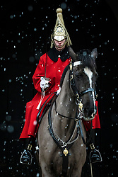 © Licensed to London News Pictures. 27/02/2018. London, UK. A member of the Household Cavalry Mounted Regiment stands on guard as snow falls on Whitehall. Severe cold, blizzards and heavy snow are expected for the rest of the week as the 'Beast from the East' brings freezing Siberian air to the UK. Photo credit: Rob Pinney/LNP