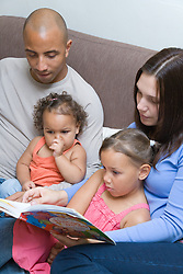 Young family sitting on the sofa together reading,