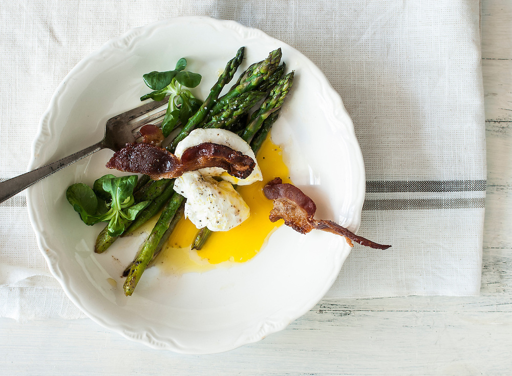 Soft poached egg with grilled asparagus, crisp bacon and mache on a white plate.