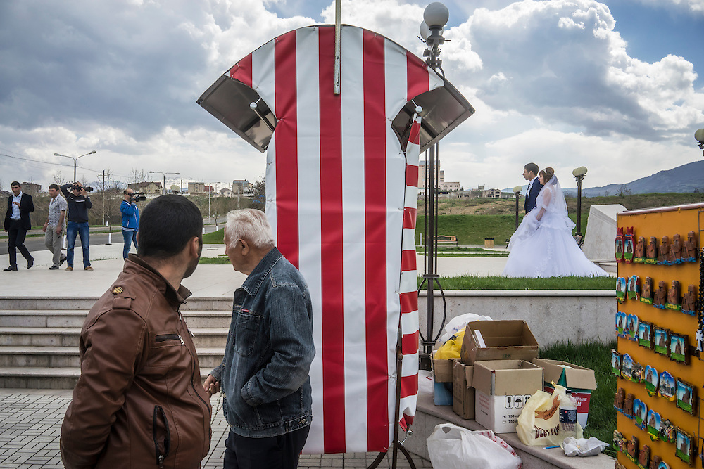 STEPANAKERT, NAGORNO-KARABAKH - APRIL 17: Groom Davit Simonyan, 24, and bride Shogher Hovsepyan, 25, take photos with family and friends at the Tatik Papik monument, a popular symbol of Nagorno-Karabakh, on April 18, 2015 in Stepanakert, Nagorno-Karabakh. Since signing a ceasefire in a war with Azerbaijan in 1994, Nagorno-Karabakh, officially part of Azerbaijan, has functioned as a self-declared independent republic and de facto part of Armenia, with hostilities along the line of contact between Nagorno-Karabakh and Azerbaijan occasionally flaring up and causing casualties. (Photo by Brendan Hoffman/Getty Images) *** Local Caption *** Davit Simonyan;Shogher Hovsepyan