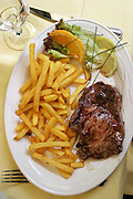 Close up of steak and fries in a restaurant near Les Invalides, Paris, France.