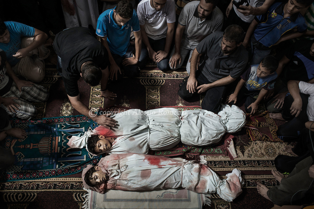 Gaza Strip, Gaza City: the bodies of Amir (D) and Mohammed (U) lying in a mosque of Gaza City as relatives pray around them. They where killed by Israeli air strike on July 9, 2014. ALESSIO ROMENZI