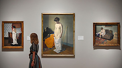 "© Licensed to London News Pictures. 27/06/2019. LONDON, UK.  A staff member passes (C) ""Nude Holding Her Gown (Femme nue retenant sa chemise à deux mains"", 1904, by Félix Vallotton. Preview of ""Félix Vallotton:  Painter of Disquiet"", an exhibition of paintings and prints Swiss artist Félix Vallotton at the Royal Academy of Arts.  Around 100 works are on show 30 June to 29 September 2019.   Photo credit: Stephen Chung/LNP"