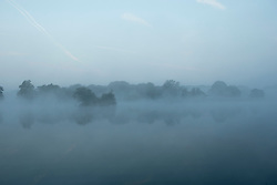 © Licensed to London News Pictures. 20/09/2015. Richmond, UK . Mist covers a lake early in the morning at Richmond park in West London as Autumn approaches. . Photo credit : Ian Schofield/LNP