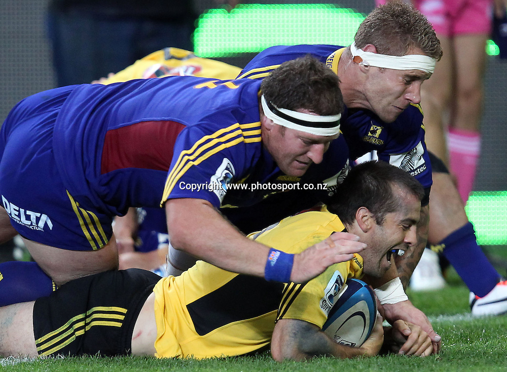 Conrad Smith of the Hurricanes crashes over for a try in the tackle of Chris King and Jarrad Hoeata.<br /> Super Rugby - Highlanders v Hurricanes, 15 March 2013, Forsyth Barr Stadium, Dunedin, New Zealand.<br /> Photo: Rob Jefferies / photosport.co.nz