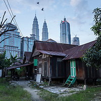 A quiet residence is seen against the against the backdrop of iconic Petronas Towers in Kampung Baru, Kuala Lumpur, Malaysia, 9 April 2017. Most of the residence of the old wooden houses in Kampung Baru are foreign worker, who just used it to sleep in between their shifts.