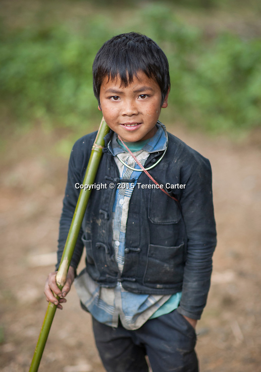 A hilltribe boy with his stick for herding cattle in the hills above Sapa, Vietnam.