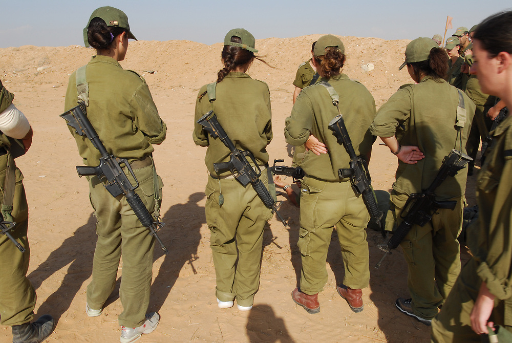 IDF woman and men reserve soldiers during training in the Negev Desert, South Israel on September 16, 2008. Following their active service, women, like men, are in theory required to serve up to one month annually in reserve duty. However, in practice only some women, mostly in combat roles, get called for active reserve duty, and only for a few years following their active service, with many exit points (e.g., pregnancy). Photo by Gili Yaar