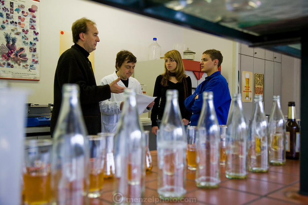 """Brewmaster Joachim Rösch speaks to lab workers who check the brewing process by sampling, at the Ganter Brewery in Freiburg im Breisgau, Germany.  (Joachim Rösch  is featured in the book What I Eat: Around the World in 80 Diets.) The caloric value of his day's worth of food in March was 2700 kcals. He is 44 years of age; 6 feet, 2 inches tall; and 207 pounds. Joachim's job requires him to taste beer a number of times during the week, and unlike in wine tasting, he can't just taste then spit it out: """"Once you've got the bitter on the back of your tongue, you automatically get the swallow reflex, so down the chute you go,"""" he says. Joachim Rösch is MODEL RELEASED."""