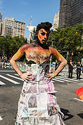New York, NY - 25 June 2017. New York City Heritage of Pride March filled Fifth Avenue for hours with groups from the LGBT community and it's supporters. A man in face paint weas a dress which seems to be made up of pages from newspapers.