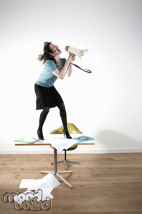 Woman standing on desk shouting through megaphone