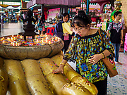 "30 DECEMBER 2017 - BANG KRUAI, NONTHABURI, THAILAND:  A woman prays to make merit for the new year at Wat Ta Khien, about 45 minutes from Bangkok in Nonthaburi province. The temple is famous for the ""floating market"" on the canal that runs past the temple and for the ""resurrection ceremonies"" conducted by monks at the temple.      PHOTO BY JACK KURTZ"