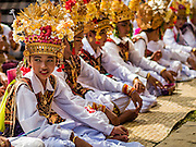 22 JULY 2016 - TENGANAN DUAH TUKAD, BALI, INDONESIA: Male dancers wait to perform after the pandanus fights in the Tenganan Duah Tukad village on Bali. The ritual Pandanus fights are dedicated to Hindu Lord Indra. Men engage in ritual combat with spiky pandanus leaves and rattan shields. They usually end up leaving bloody scratches on the combatants' backs. The young girls from the community wear their best outfits to watch the fights. The fights have been traced to traditional Balinese beliefs from the 14th century CE. The fights are annual events in the Balinese year, which is 210 days long, or about every seven months in the Gregorian calendar.    PHOTO BY JACK KURTZ